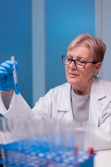 Senior doctor discovering genetic infection and analysing a test tube for medical expertise
