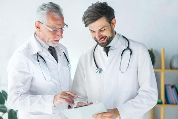 Senior doctor explaining colleague data on clipboard