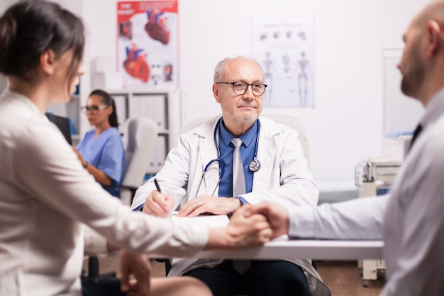 病院の診療所での健康診断中に若いカップルに悪い知らせを与える先輩医師。手をつないでいる夫と妻。患者のx線を見る看護師。