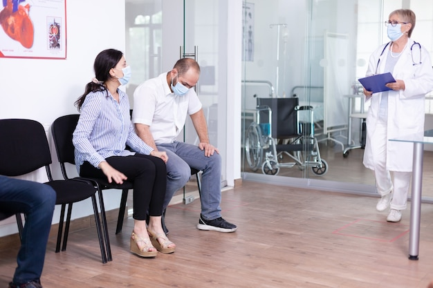 Senior doctor giving bad news to young couple in hospital waiting area