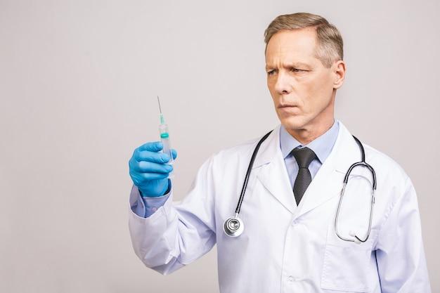 Старший доктор в голубых перчатках держит медицинский шприц для впрыски изолированной над серой предпосылкой.