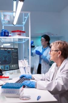 Старший врач в белом халате работает на компьютере в лаборатории открытий