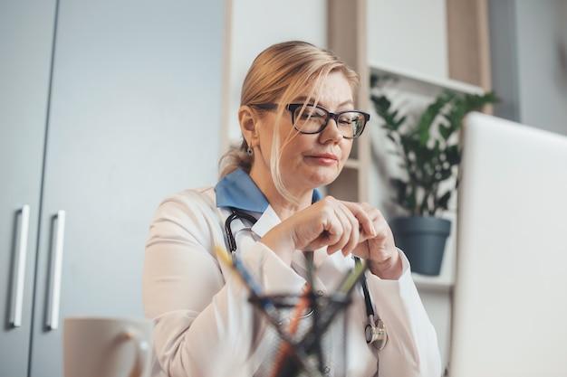 Старший врач использует ноутбук в офисе, работая удаленно с пациентами онлайн