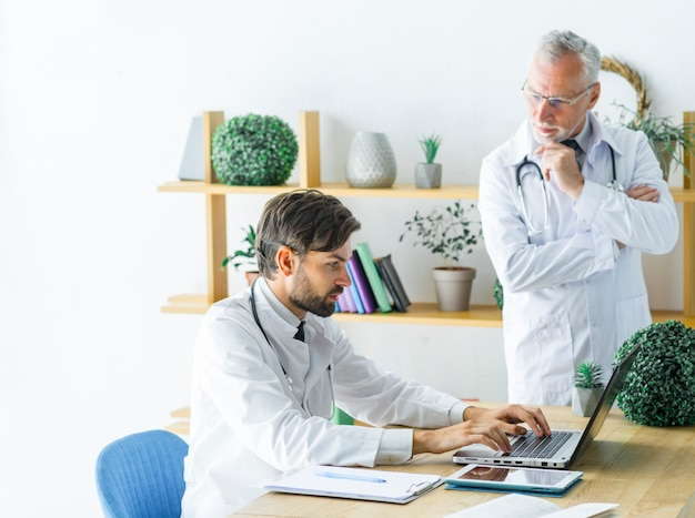 Senior doctor looking at young colleague using laptop
