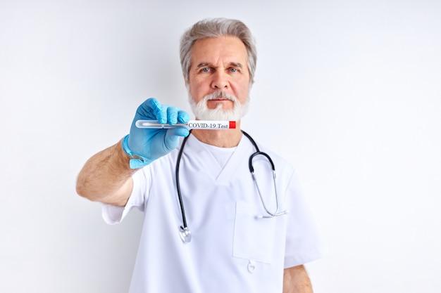 Старший врач мужчина держит в руках результат теста, фокусируется на пробирке
