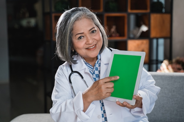 Senior doctor pointing screen of tab