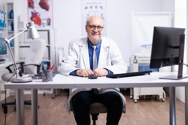 Старший врач улыбается в камеру, сидя в медицинском кабинете во время видеовстречи, профессиональный мужчина в белом халате разговаривает в чате конференц-связи, консультируя пациента онлайн, глядя на веб-камеру