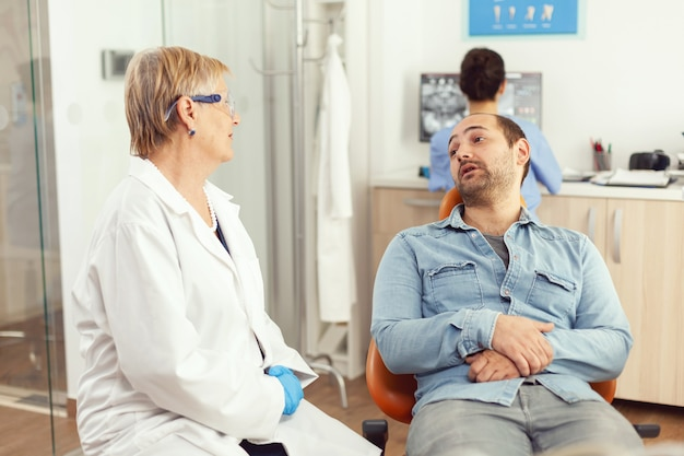 Senior doctor stomatologist discussing with patient before examining oral health while sitting on dental chiar in hospital stomatology office