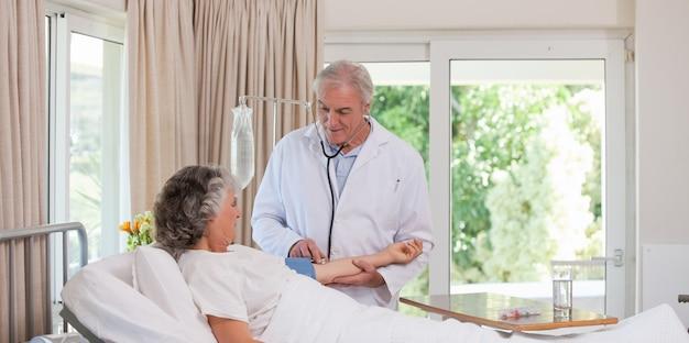 彼の患者の血圧を取っている上級医