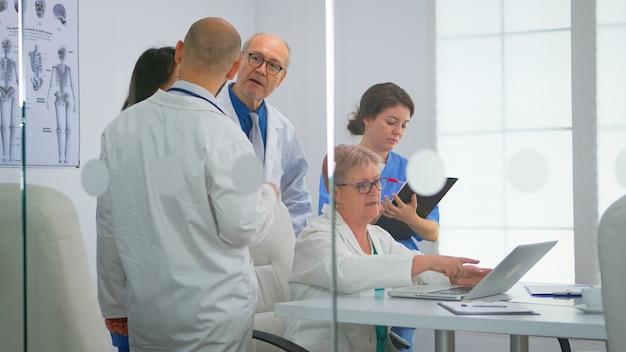 病院の会議室での医療ブレーンストーミング中に患者の治療を同僚に説明するラップトップを使用している先輩医師。職場での問題記録の診断について話し合う医療チーム。