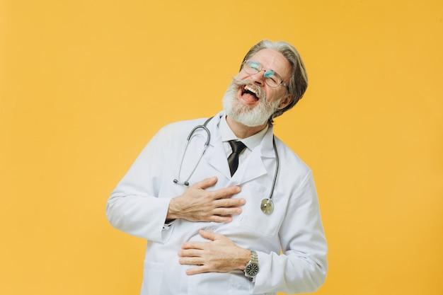 Старший врач в белом халате и стетоскоп, изолированные на желтой стене, держась за руки на живот и смеется