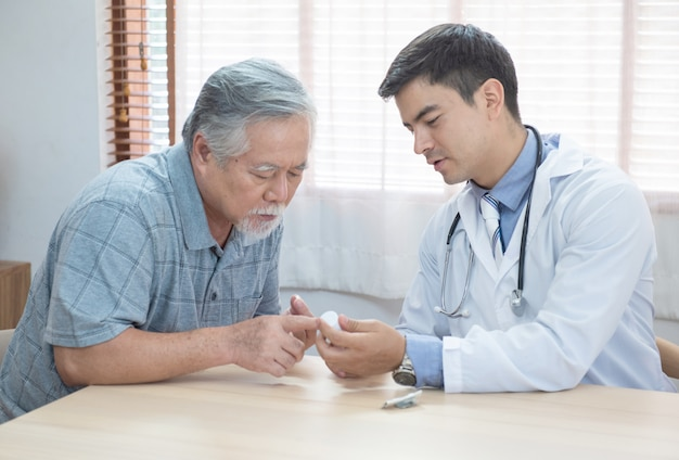 Senior elder asian man asking young caucasian doctor about indications and contraindications of new medicine, healthcare and medicine concept with copy space.