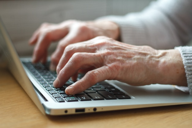 Senior elderly business woman working on laptop.