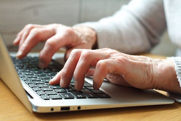 Senior elderly business woman working on laptop.