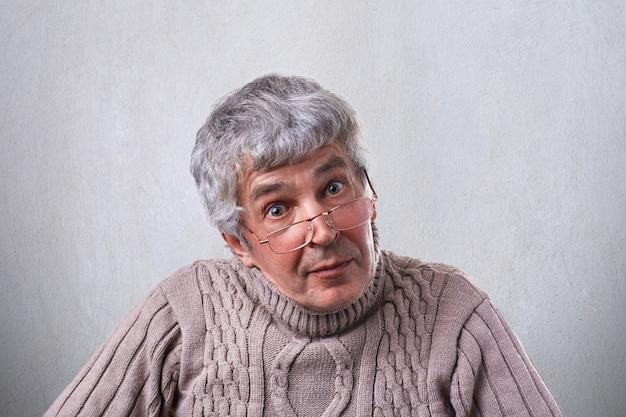 Старший, пожилой мужчина в очках, глядя с широко открытыми глазами, с умным выражением
