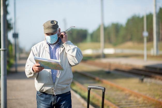 Старший пожилой мужчина смотрит на карту путешествия во время пандемии