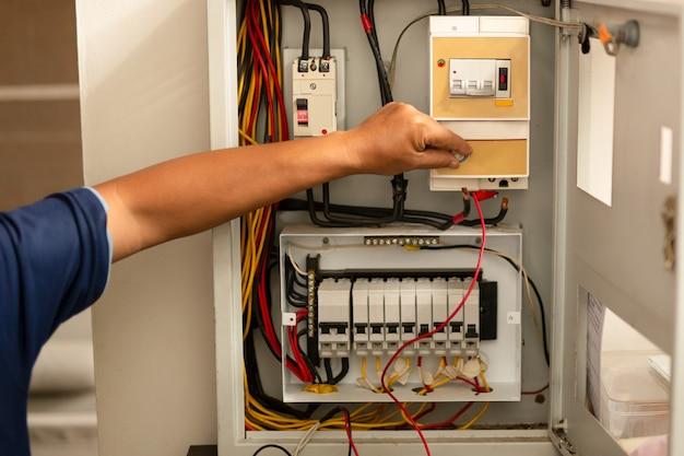 Senior electrician measuring voltage in fuse board.