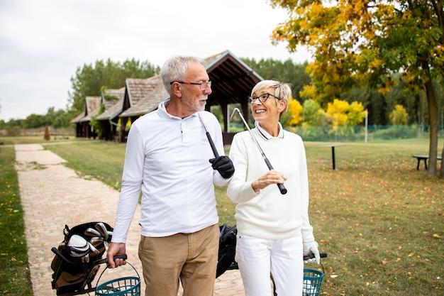 Старшие элегантные люди с удовольствием проводят свободное время на пенсии, играя в гольф.
