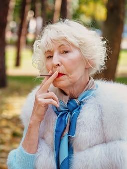 Senior elegant stylish fashionable woman with grey hair in fur coat outdoor smoking cigarette