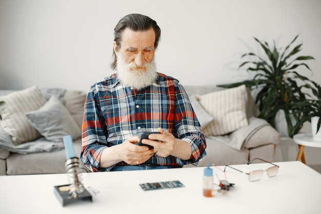 Senior engineer check phone after repairment. reirment of gadgets.