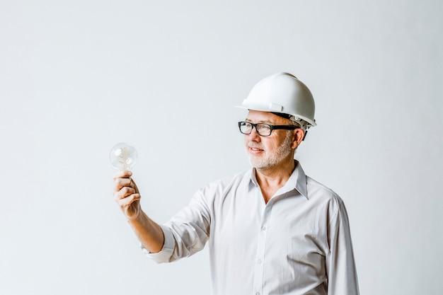 Senior engineer holding a light bulb