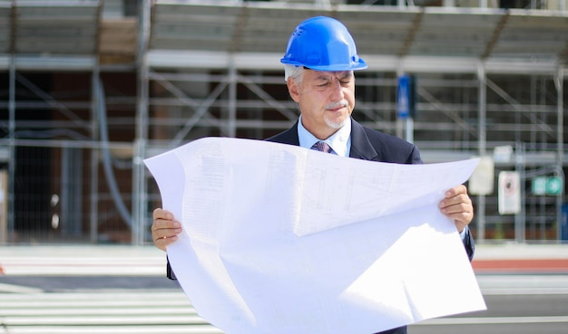 Senior engineer reading a blueprint i front of a construction site