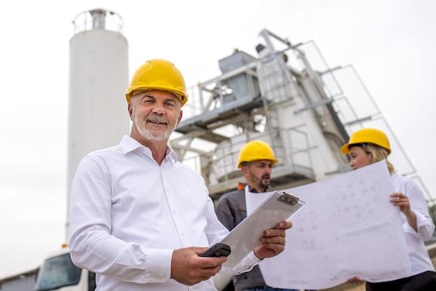 Старший инженер улыбается со своими коллегами на строительной площадке