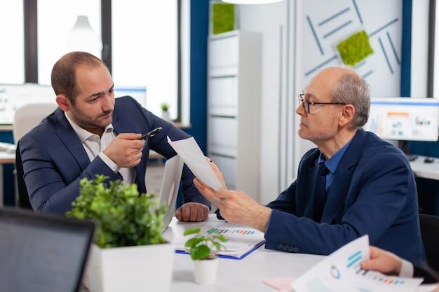 ブリーフィング中に会議でドキュメントを保持している同僚と話し合う上級起業家ビジネスマンが新しいスタートアップ企業の財務戦略について同僚とアイデアを話し合う