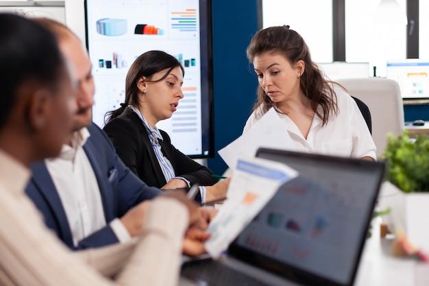 브리핑 중 회의에서 문서를 들고 동료와 논의하는 고위 기업가 사업가는 새로운 시작 회사를 위한 재무 전략에 대해 동료와 아이디어를 논의합니다.