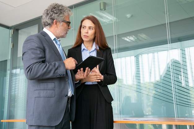 직원과 논의하고 태블릿을 들고 회의실에 서있는 고위 임원