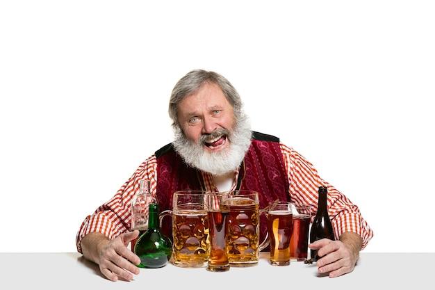 白い背景で隔離のビールとシニアエキスパート男性バーマン。