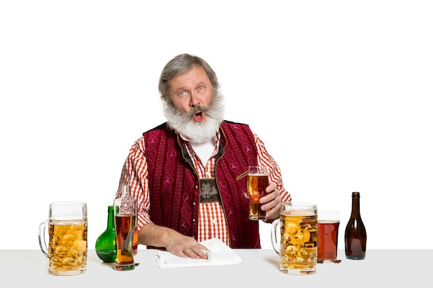 The senior expert male barman with beer  isolated on white wall. international barman day, bar, alcohol, restaurant, beer, party, pub, st. patrick's day celebration concept