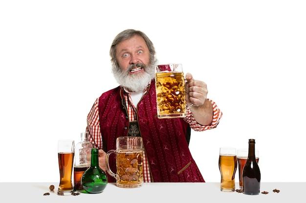 Il barista maschio esperto senior con birra in studio isolato su bianco