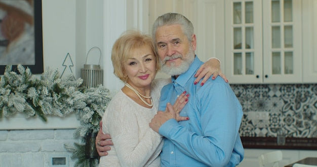 Senior family couple hugging, smiling, elderly old adult grandparents husband and wife happy faces embracing at home