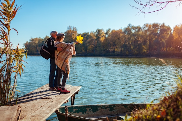 Senior family couple walking by autumn lake. happy man and woman enjoying nature and hugging on pier