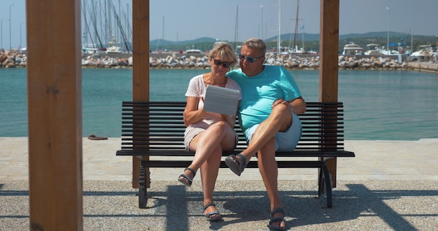 Senior family couple with pad on waterfront