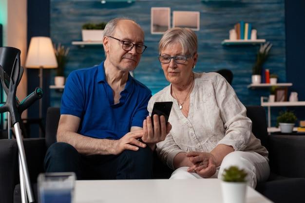 スマートフォンの画面表示を見ている2人のシニア家族