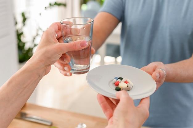 유리 물로 점심 식사 전에 식품 보조제 약을 복용하는 노인 가족은 자른 프레임을 닫습니다.
