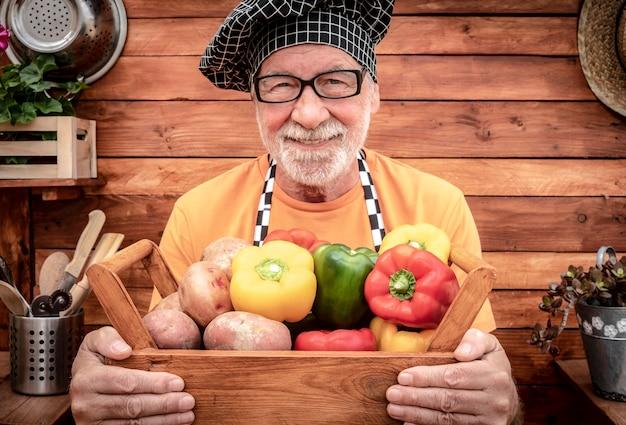 収穫したローフード野菜、ジャガイモ、ピーマンがいっぱい入った木製のバスケットを持っているシニアファーマー