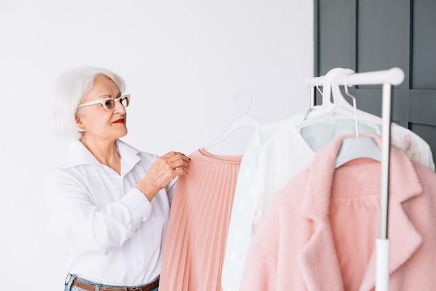 シニアファッションエレガンス。ショールームコレクション。スタイリッシュな服のラックでスマートな老婦人。