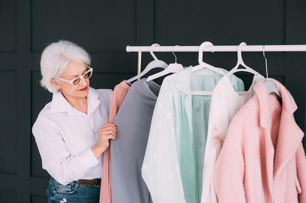 シニアファッションスタイル。ショッピングと衣料品のオプション。衣装を選ぶおばあさん。