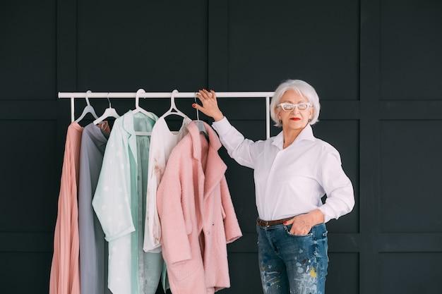シニアファッションスタイル。ショッピング体験。衣装を選びながらカメラを見ているおばあさん。
