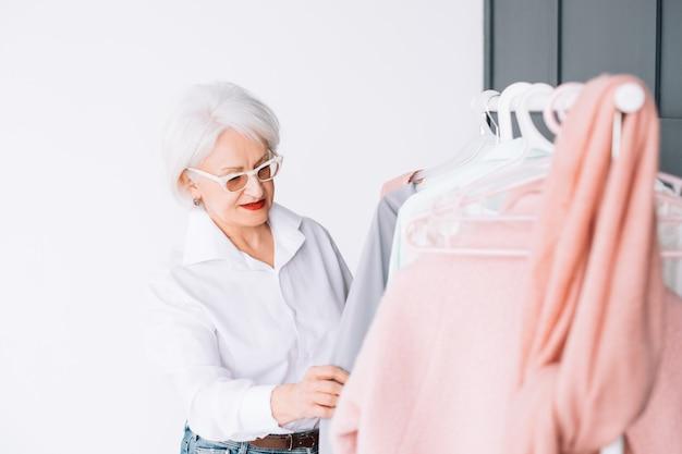 シニアファッション。スタイリッシュなショールーム。衣類の棚を通して見ている眼鏡の賢い年配の女性。
