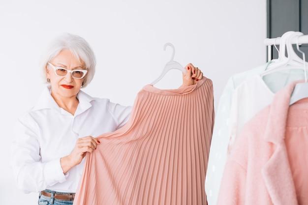 シニアファッショントレンド。個人的なスタイル。服のオプションを示す自信のある年配の女性。