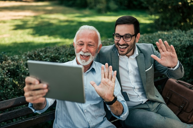 Senior father and adult son having a video call outdoors.