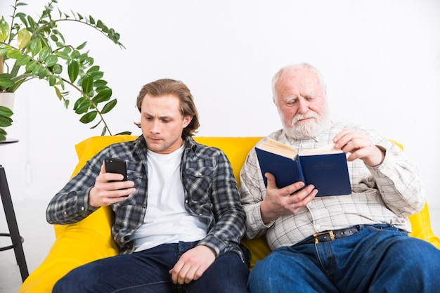 Senior father and adult son relaxing separate