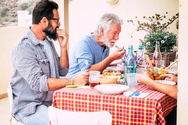 愛と友情を楽しんでいる屋外テラスで家で一緒に昼食をとっている先輩の父と大人の息子-お祝いと家族と幸せの概念を共有する-混合世代が一緒に食べる