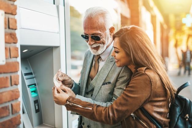 시니어 아버지와 그의 딸은 현금 인출기를 함께 사용하여 돈을 인출합니다. 그들은 행복하다. 밝고 화창한 날.