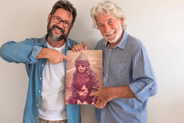 Старший отец и зрелый сын в пустой квартире с движущимися ящиками улыбаются, держа старые фотографии того и другого, когда были намного моложе - концепция семьи и любви