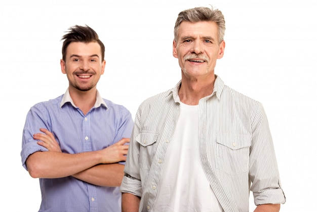 Senior father with adult son smiling.